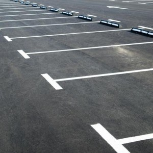 Markings on asphalt pavement indicating the parking lot in front of the store
