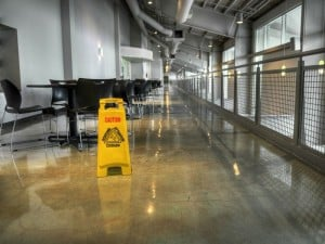"A yellow ""caution wet floor"" sign stands on top of a beautifully mopped tile floor in a commercial building in Orange County. The floor was just recently maintained by Prestige Property Services and their commercial cleaning services team."