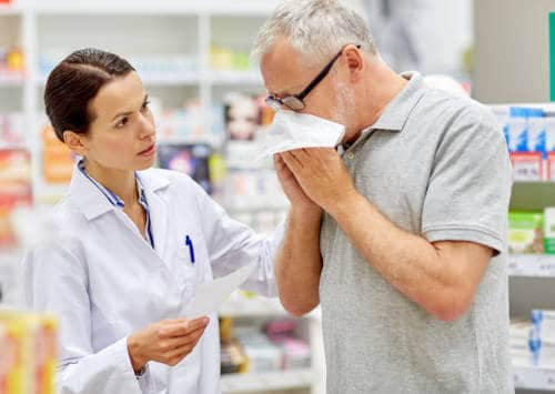 janitorial company, medicine, pharmaceutics, health care and people concept - pharmacist and sick senior man with flu blowing nose at pharmacy