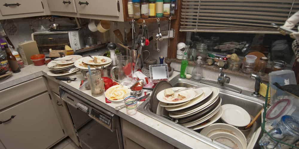 A gross, messy kitchen with dishes all over the counter and in the sink. This house definitely needs professional cleaning services